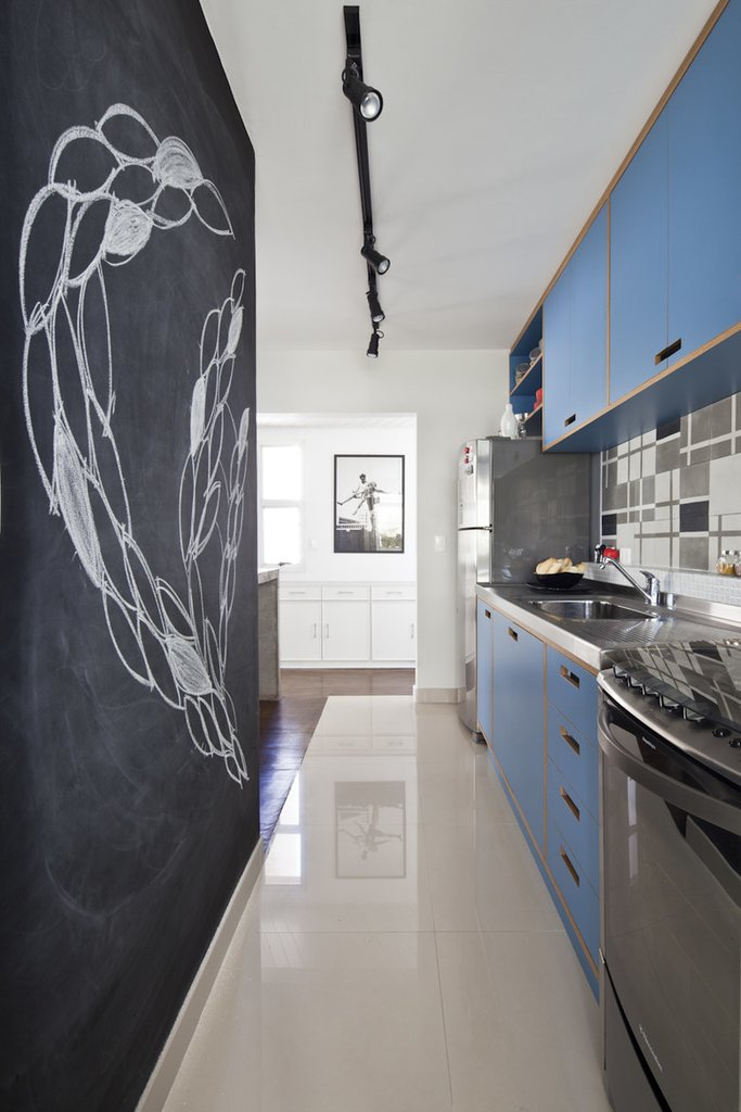 Кафельный пол определяет кухню в открытой планировке. Интересна и полезна черная стена на которой можно писать и рисовать мелом