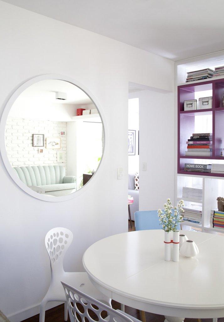Круглое зеркало на стене рядом с круглым обеденным столом выглядит как окно