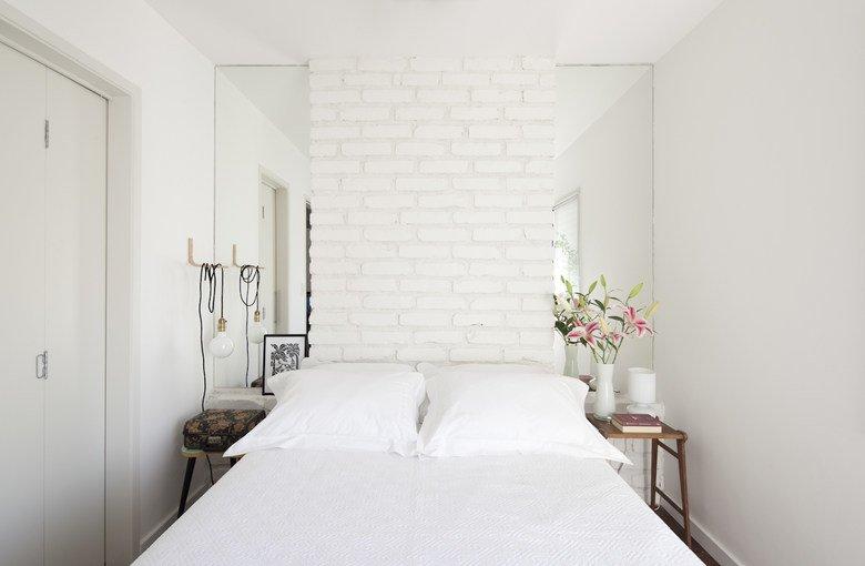 В спальне изголовье кровати из крашеного в белый кирпича обрамлено узкими вертикальными зеркалами, которые придают глубины небольшому помещению.