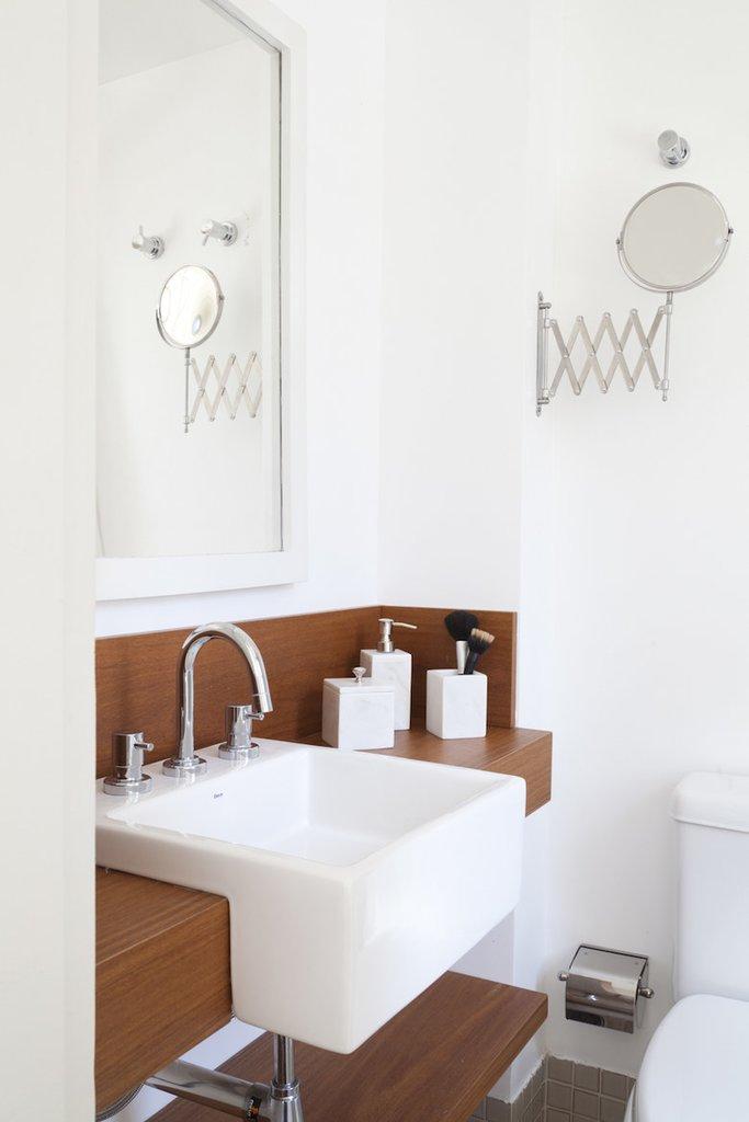 Ванная комната выдержана в белых и серых тонах. Умывальник выступает за деревянную полку на которой установлен.