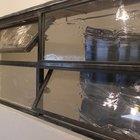 Окно с поворотными секциями в черной стальной раме также разработано и изготовлено дизайнерами фирмы специально для данной кухни..
