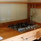 В данной кухне вместо кухонного фартука предусмотрен стеклянный экран защищающий стену рядом с варочной поверхностью.