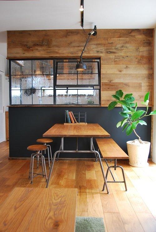 Элегантный обеденный стол в стиле лофт со скамьей и табуретками расположен рядом с модной сейчас стеклянной перегородкой разделяющей кухню и столовую.