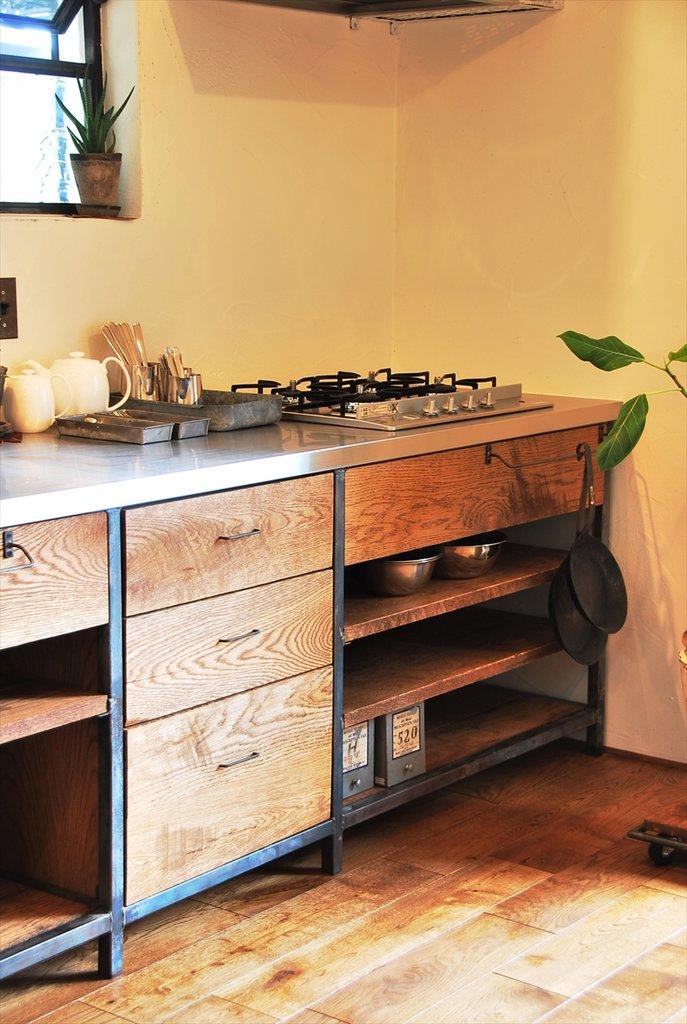 На фото хорошо видна достаточно простая конструкция самой кухни. Вешалки тут используются не только для полотенец, но и для сковородок.