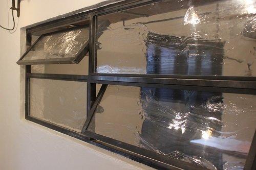 Окно с поворотными секциями в черной стальной раме также разработано и изготовлено дизайнерами фирмы специально для данной кухни