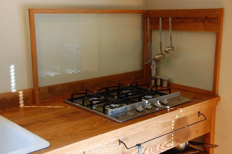 В данной кухне вместо кухонного фартука предусмотрен стеклянный экран защищающий стену рядом с варочной поверхностью