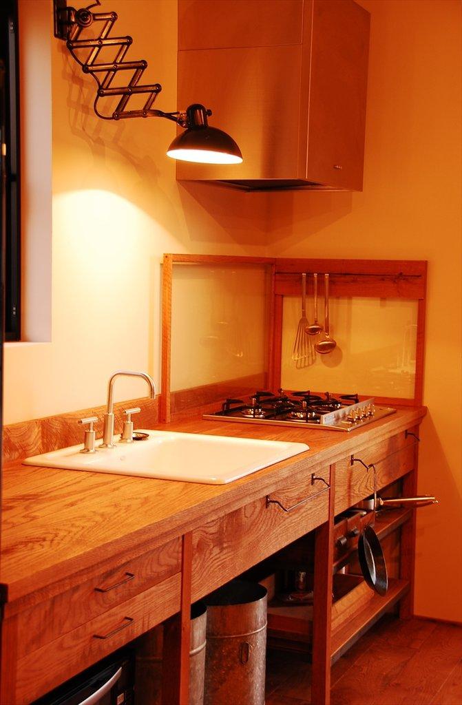 Выдвижная лампа является почти обязательным атрибутом всех кухонь фирмы. Кроме того что она интересно выглядит, лампа очень хорошо освещает рабочую поверхность кухни и легко подстраивается под потребности повара