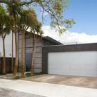 Фасад дома с широким въездом в гараж и забором из вулканического камня в оцинкованых сетках.