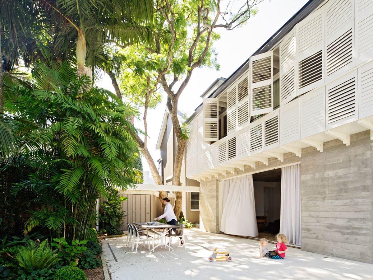 Деревья сада за домом затеняют двор и позволяют проводить много времени на улице. Этому способствуют и широкие раздвижные стеклянные двери