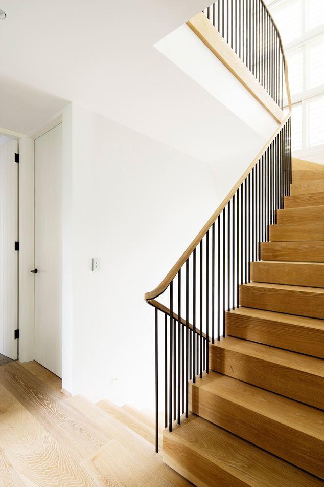 Дубовая лестница залитая светом соединяет три этажа резиденции.