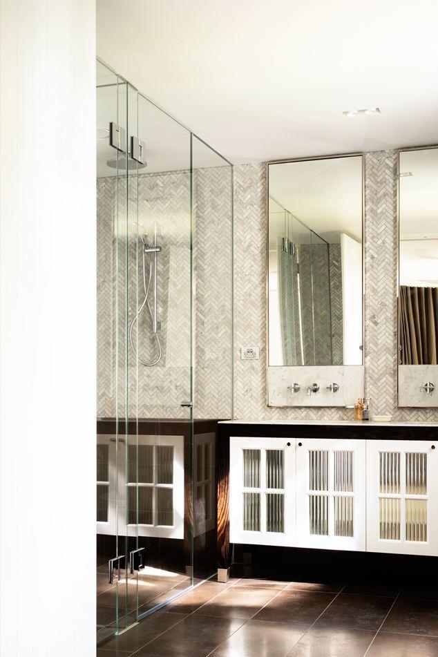 Елочная мозаика из мраморной плитки, никелевое покрытие рам зеркал, кафельный пол, остекленные шкафчики (стекло повторяет кухонные шкафчики) дают ванной комнате широкую палитру цветов, материалов и текстур.