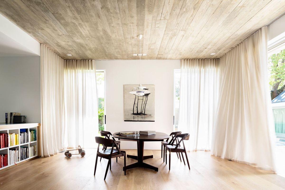 В столовой на первом этаже занавески защищают от солнца. Бетонный потолок с отпечатками опалубки из дерева лиственных пород контрастирует с дубовым полом.