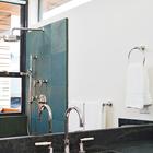 Даже из ванной комнаты открывается вид на океан через узкое окно. (пляжный,индустриальный,лофт,винтаж,стиль лофт,индустриальный стиль,современный,архитектура,дизайн,экстерьер,интерьер,дизайн интерьера,мебель,ванна,санузел,душ,туалет,дизайн ванной,интерьер ванной,сантехника,кафель)