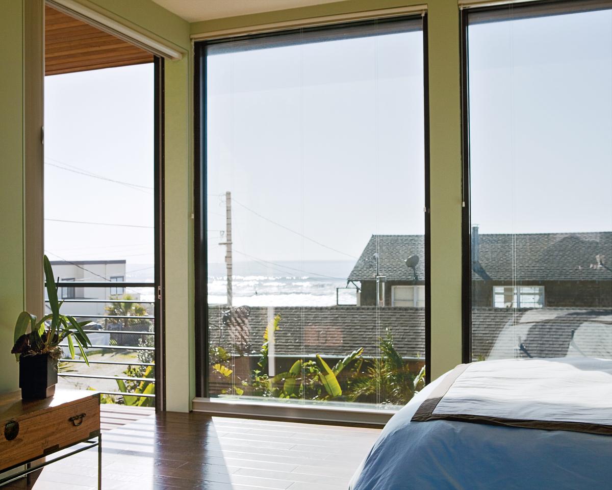 В спальне большие окна от пола до потолка открывают вид на океан