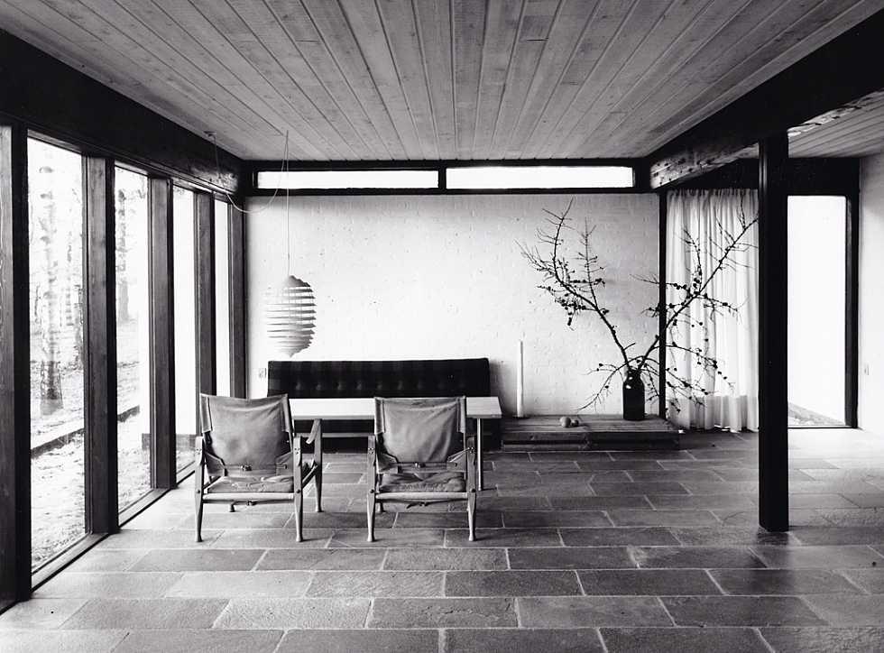 Гостиная с характерными для архитектуры 60-х большими остеклениями и бетонными плитами на полу.