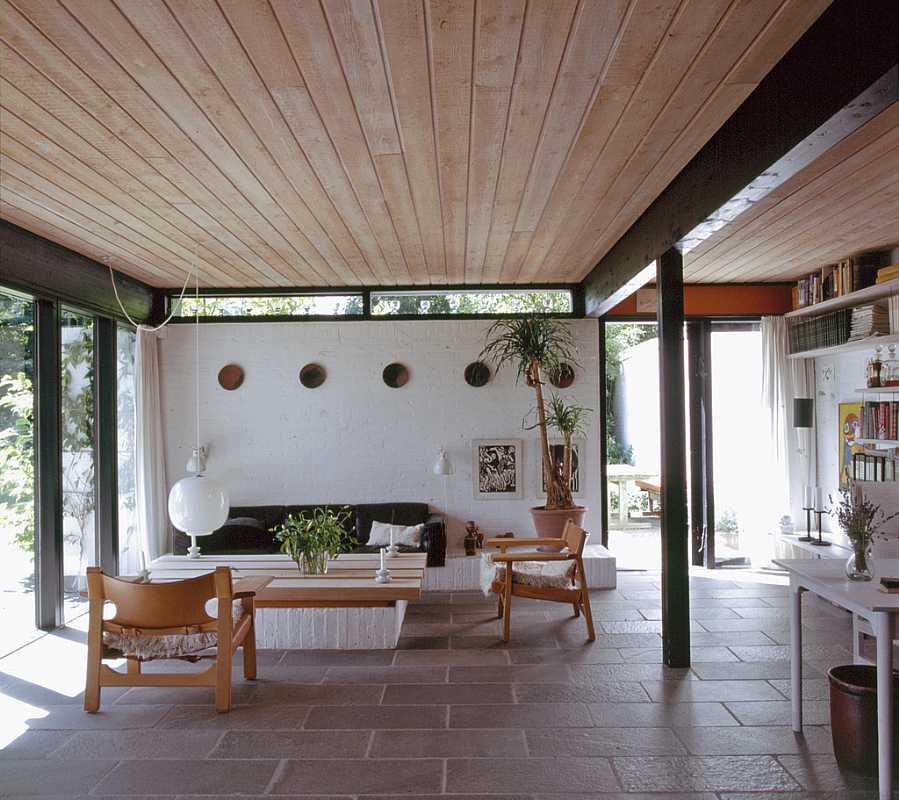 Натуральные цвета гостиной с белыми побеленными стенами, деревянным потолком делают интерьер приятными и ненадоедающим.
