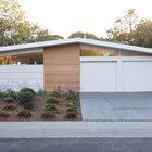 Фасад дома. В этой части дома расположены гараж, который видно, и кухня, треугольное окно которой расположено в левой части фасада.