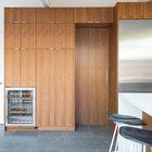 Теплые темные деревянные оттенки кухонной мебели смягчают холодность белых стен, потолка, столешницы и серого пола.