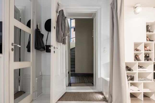 Гардероб расположился прямо у входа, а дверь в ванну сделана зеркальной и заменяет зеркало во весь рост у входа
