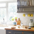 Лакированная деревянная кухонная столешница контрастирует с темным цветом кухонных шкафчиков и сушилкой для тарелок.