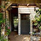 У входа в дом находится терраса с примитивной перголой. (вход,прихожая,на открытом воздухе,патио,балкон,терраса,эклектика,смешение стилей,архитектура,дизайн,экстерьер,мебель)