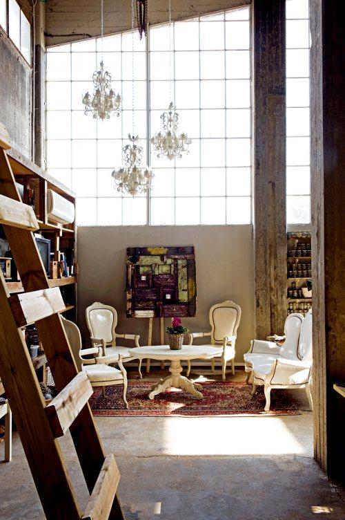 Эклектичная гостиная с грубой лестницей, неокрашенными опорами, высоким потолком и причудливые люстры и мебель в стиле барокко.