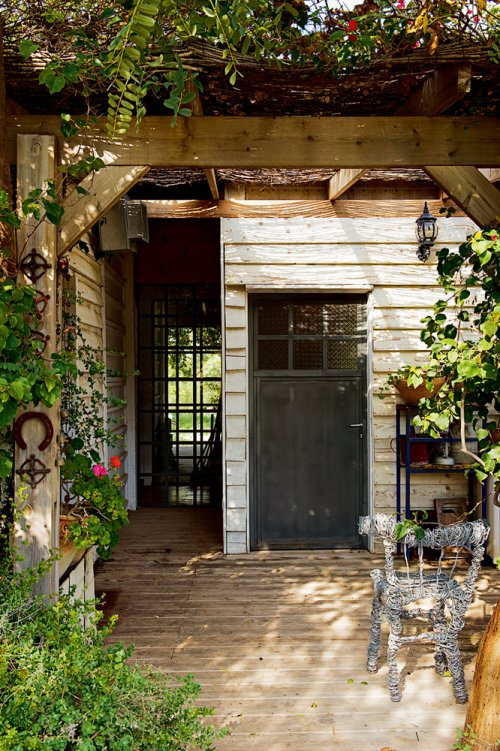 У входа в дом находится терраса с примитивной перголой.